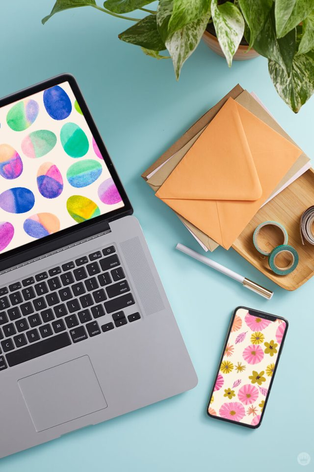 April 2020 digital wallpapers: Easter egg and floral designs displayed on laptop and mobile phone; photo also includes plant, envelopes, office supplies