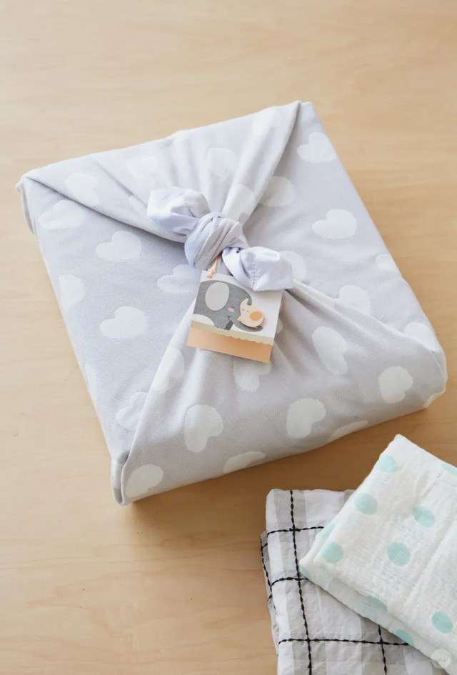 Box wrapped in gray, heart-covered blanket with illustrated elephant gift tag.