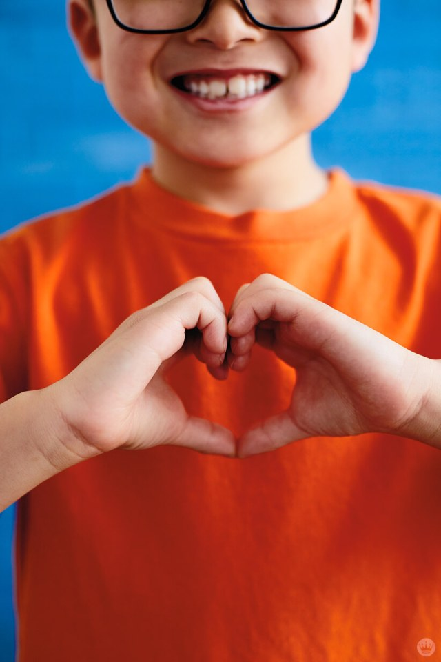 "Back-to-school picture ideas: boy making ""heart hands"""
