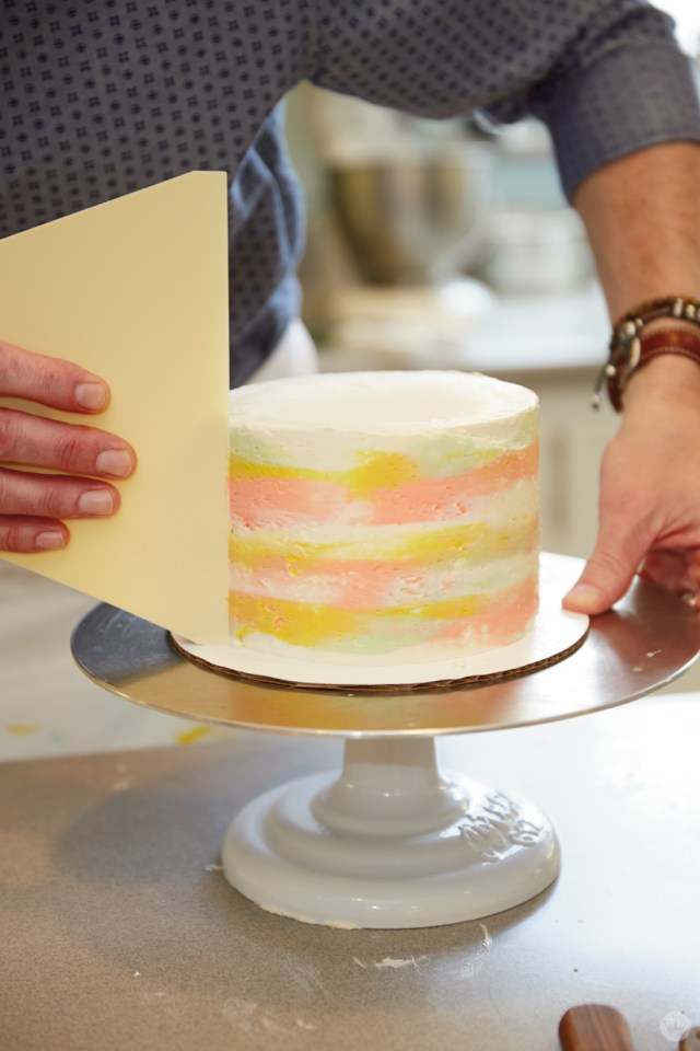 Using a large bench scraper to blend different colors of buttercream on the sides of a layer cake