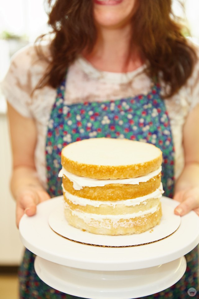 Cake decorating: four layers of cake stacked and filled with buttercream frosting