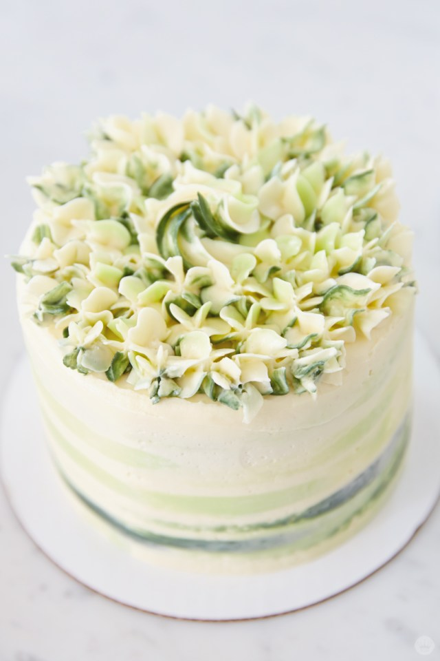 The top of a green and white watercolor cake, decorated with white and green flowers
