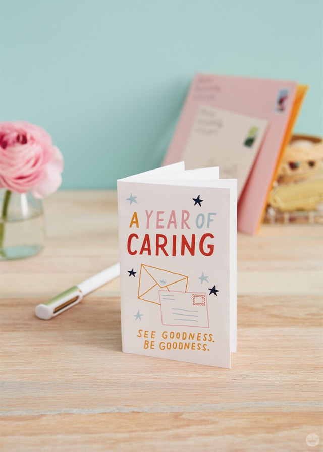 """A Year of Caring"" booklet on a table with flowers and letters in the background 