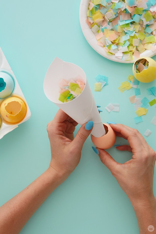 Using a paper funnel to fill a hollow egg with confetti for DIY cascarones | thinkmakeshareblog.com