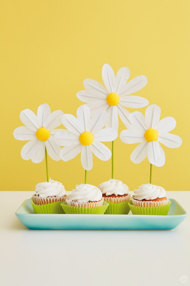 Finished DIY Daisy Cake Toppers in white frosted cupcakes