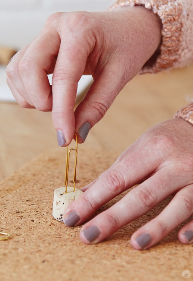 Adding a paper clip to a cork for Candlestick Christmas card holders