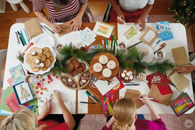 Signing and sending holiday greetings at a Christmas card party