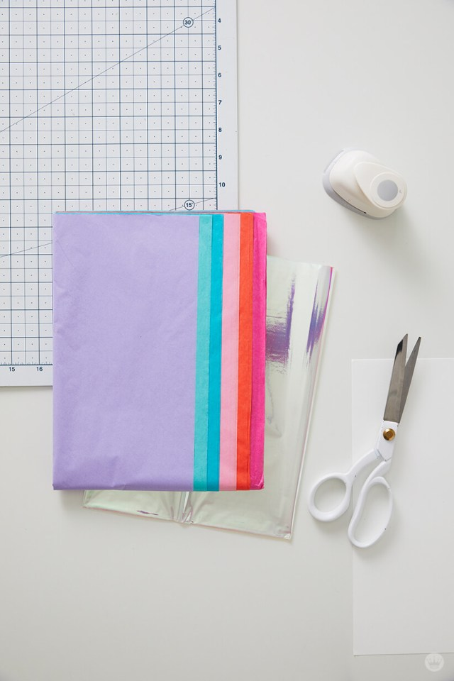 Supplies for DIY tissue paper confetti: tissue paper, hologram paper, scissors, construction paper, circle punch, cutting board