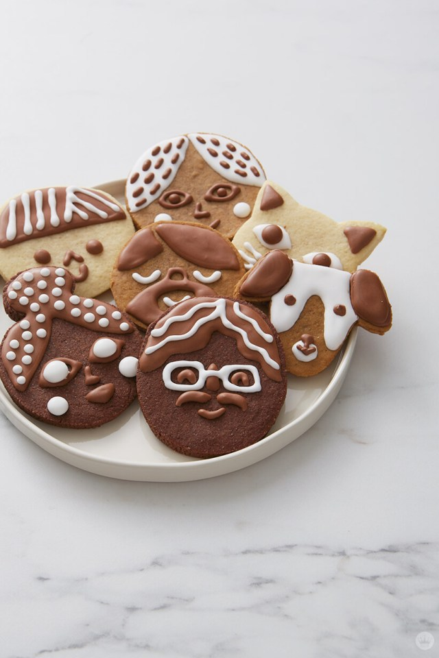 A plate of cookie faces decorated to look like friends, family and pets | thinkmakeshareblog.com