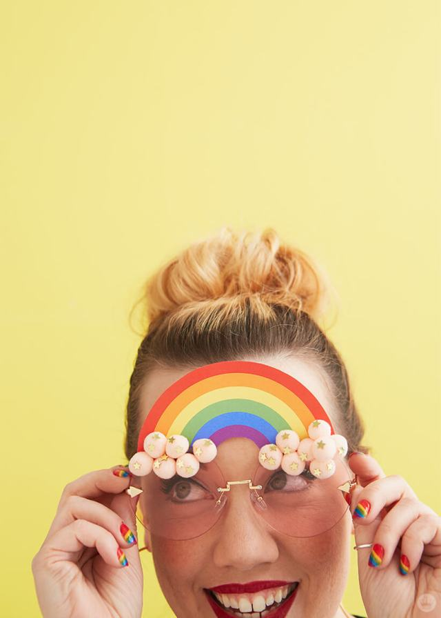 Hallmark Designer Katie K. wearing DIY Pride Sunglasses with a rainbow and pink pom pom clouds | thinkmakeshareblog.com