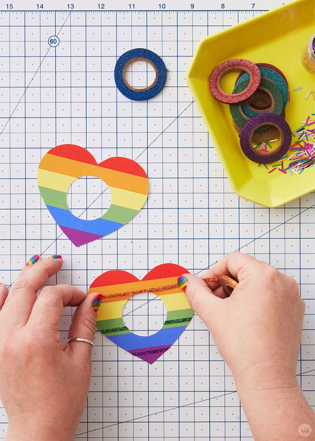 Adding glitter washi tape to a cut out heart for the DIY Pride Sunglasses | thinkmakeshareblog.com