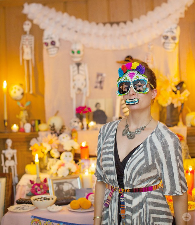 Dressed for a Day of the Dead celebration with a sugar-skull inspired mask, standing in front of a decorated ofrenda