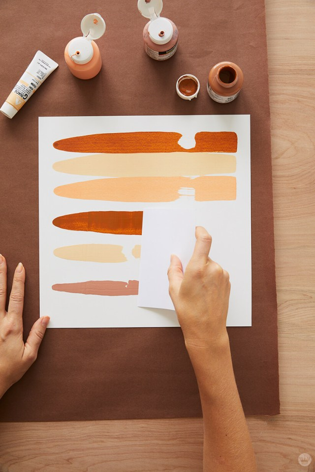 Sliding the paint splootches across paper to make the easy DIY fall decor | thinkmakeshareblog.com