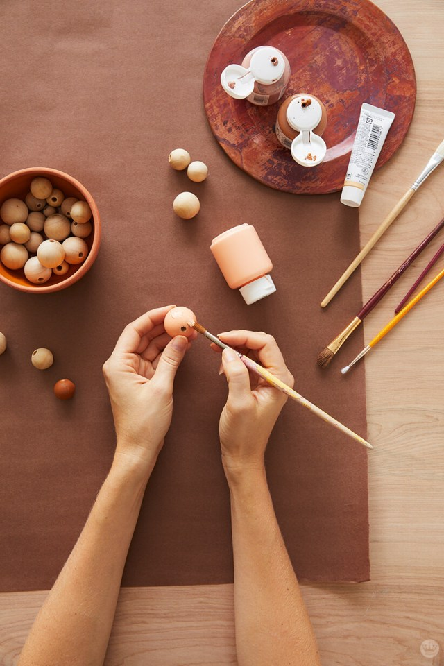 Painting wooden beads in our fall color palette for the garland | thinkmakeshareblog.com