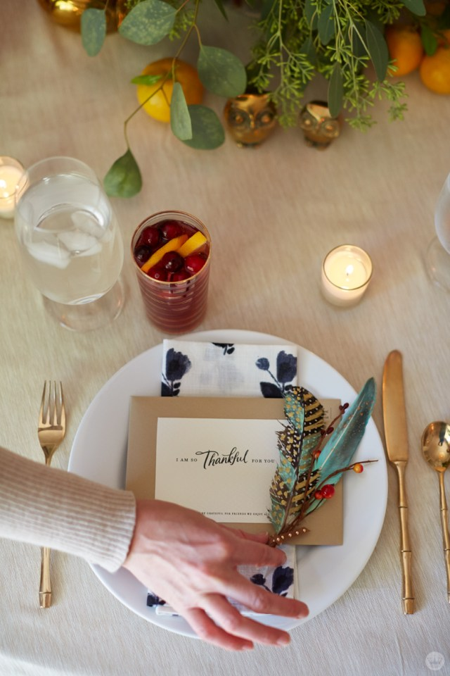 Place setting with note and painted feather arrangement