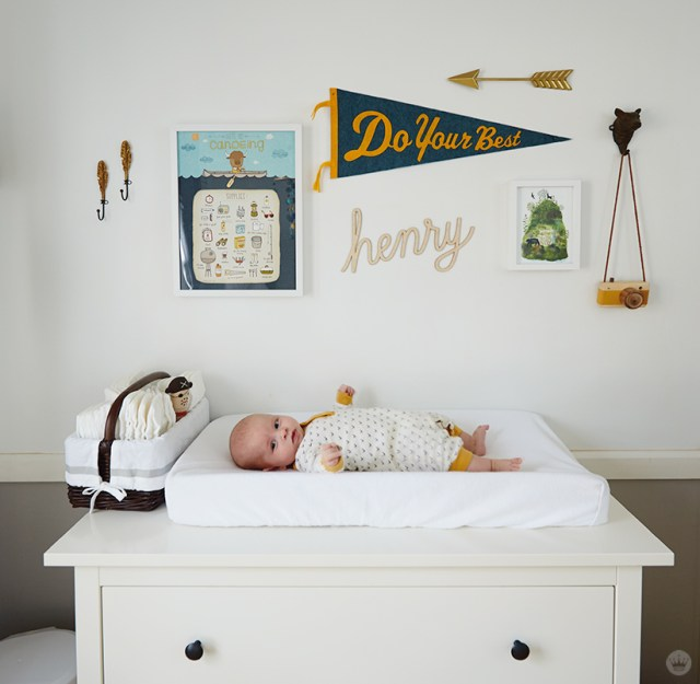 """Tips for displaying art: A gallery wall over a baby on a changing table features a pennant (""""Do your best""""), the word """"henry"""" in rope letters, a print about canoeing, and other pieces of art"""