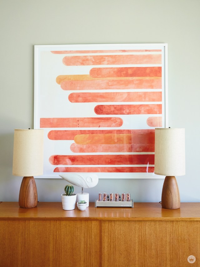 Tips for displaying art: A large square framed piece of art (featuring orange stripes) hangs over a wooden sideboard that holds two lamps, small potted succulents, a bird sculpture, and modern digital clock