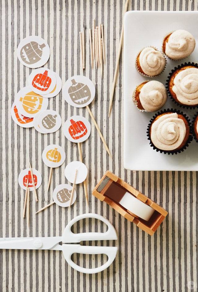 Make our free Halloween Cupcake Toppers by cutting out toppers and sticking toothpicks to the backs with tape.