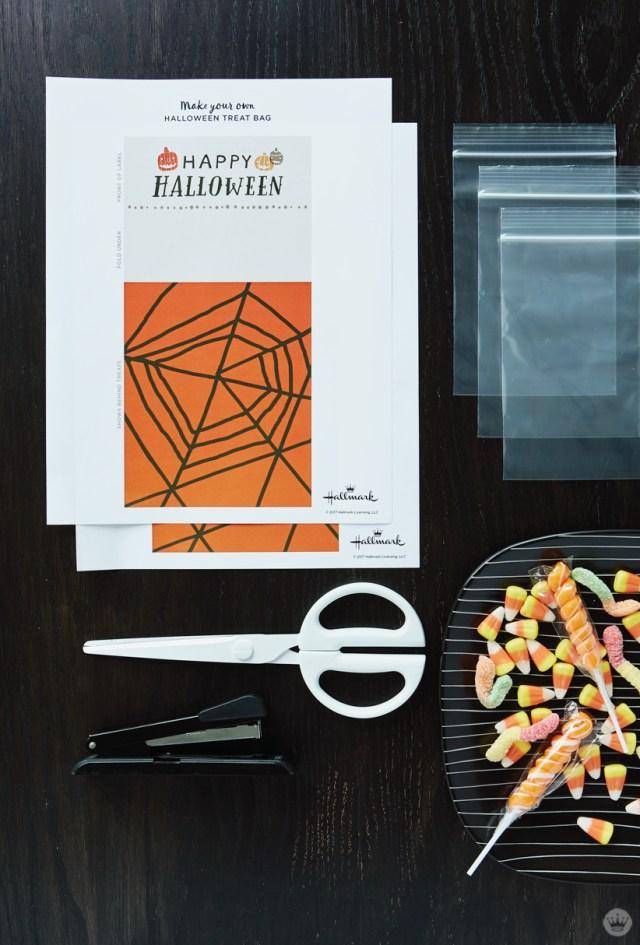 Supplies for free printable Halloween treat bags: printed design, bags, scissors, stapler, snacks