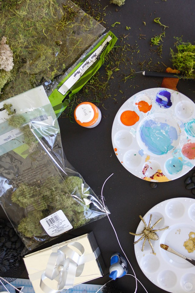 Supplies for miniature haunted houses: Moss, glitter-covered spiders, paint, glue, craft knife