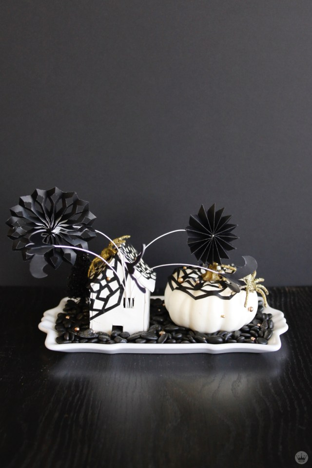 Miniature Haunted House Halloween decorations: Abstract black and white house and matching pumpkin with gold glitter spiders crawling on top. Black paper bats and flowers popping out of window on wires.