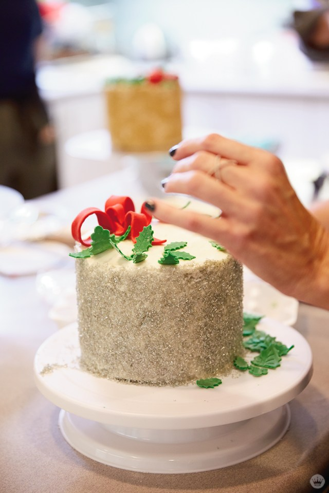 Adding fondant holly leaves to a frosted layer cake