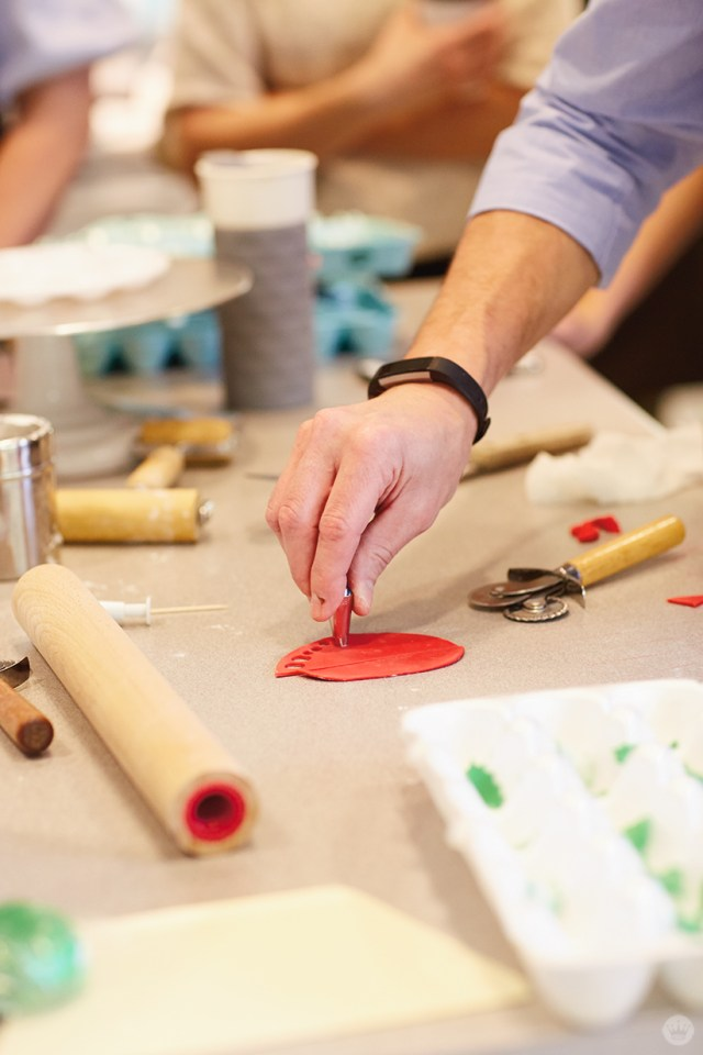 Cutting holly berries from red fondant using a round piping tip