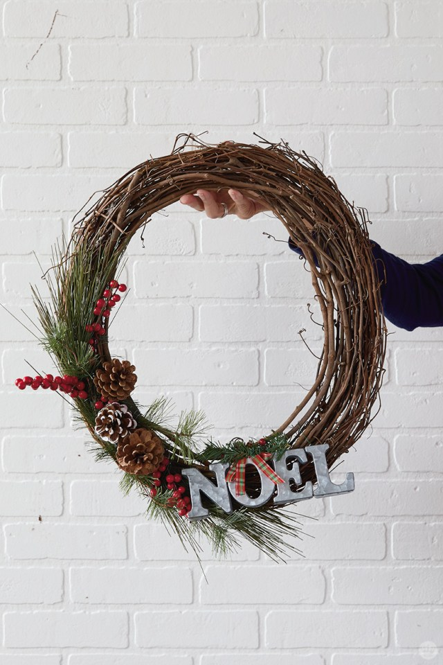 "Modern Christmas wreath ideas: Grapevine wreath with ""NOEL"" and pine greenery"
