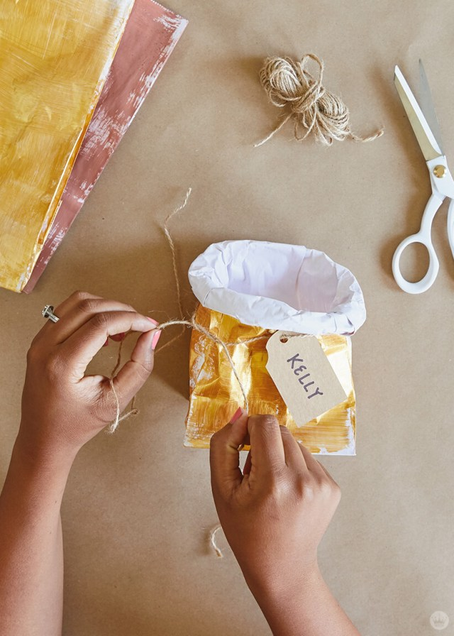 Using twine to attach a gift tag to a DIY Paper Plant Bag | thinkmakeshareblog.com
