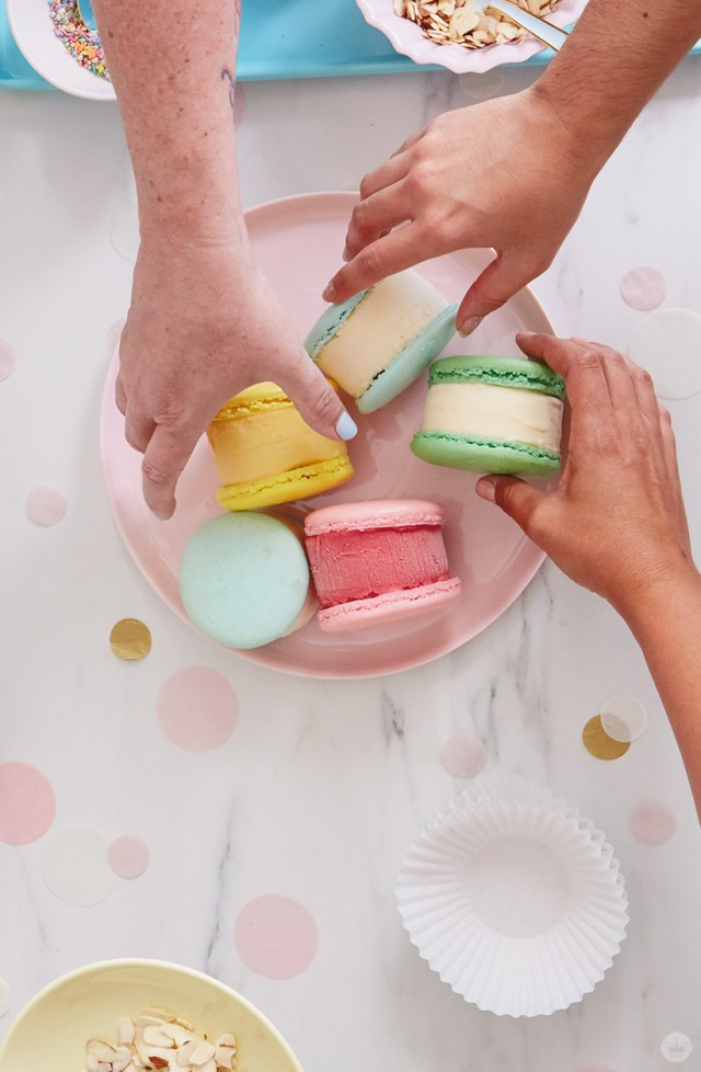 Grabbing macaron ice cream sandwiches to roll them in edible toppings and sprinkles