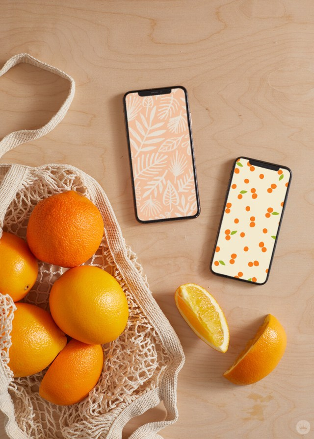 two of our June Wallpapers on iphones, laying next to a net bag with oranges | thinkmakeshareblog.com