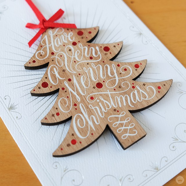 Wooden tree ornament on white greeting card.