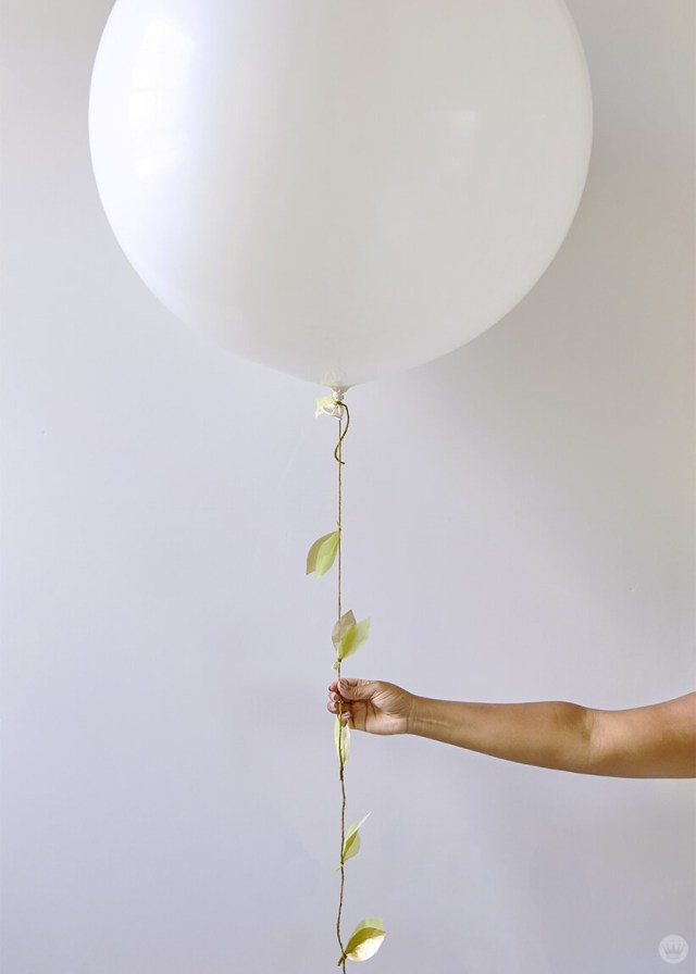 the DIY paper vine garland attached to a giant white balloon | thinkmakeshareblog.com