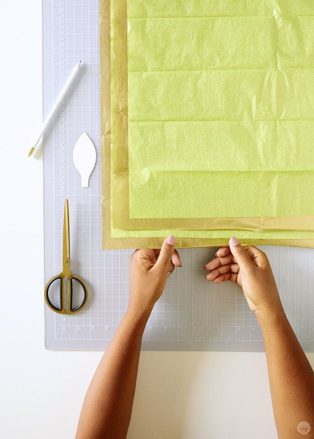 layering tissue paper sheets for the DIY paper vine garland | thinkmakeshareblog.com