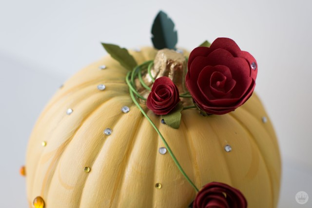 Detail: Yellow pumpkin wrapped with artificial red roses and encrusted with yellow gems