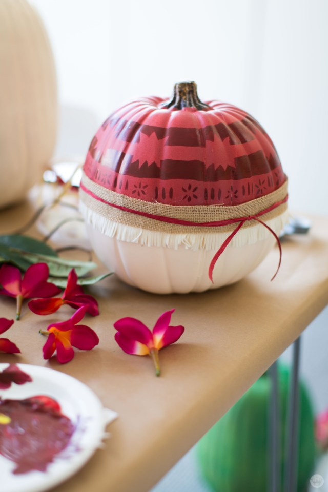 A pumpkin decorated with burlap and Polynesian-inspired designs