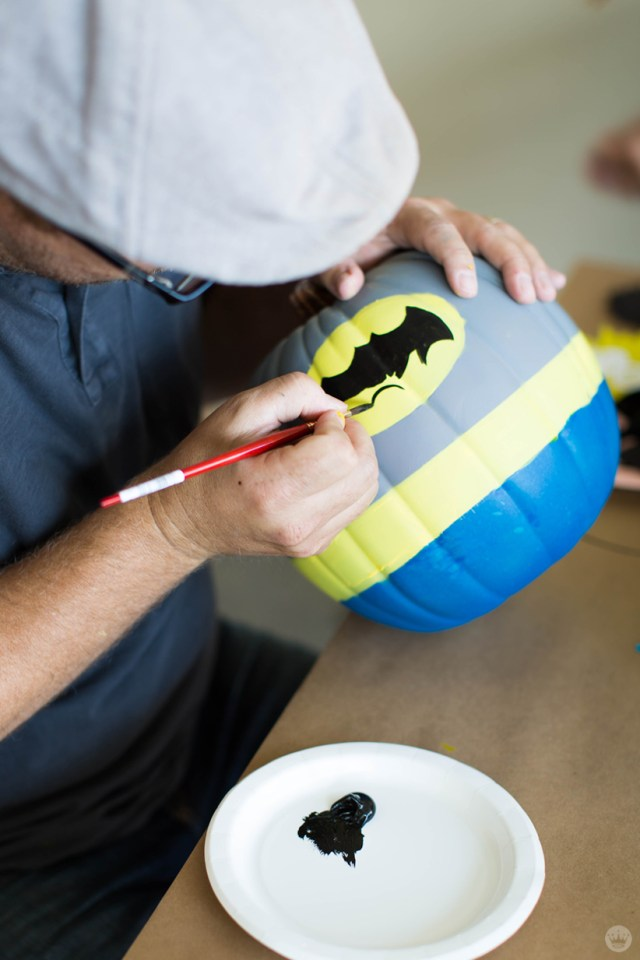 Painting an iconic symbol on a Batman-inspired pumpkin