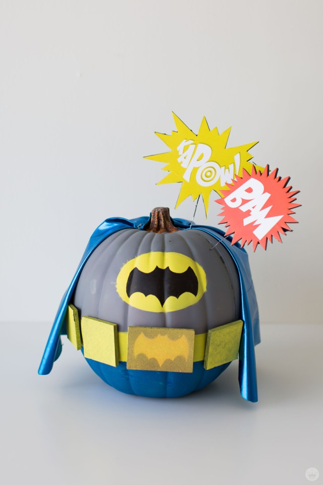 "Pumpkin painted in gray, blue, and yellow—including a blue fabric cape—to resemble Batman's costume from the 1960s television show based on the DC comic book character. Starbursts on top of the pumpkin say ""KAPOW!"" and ""BAM."""