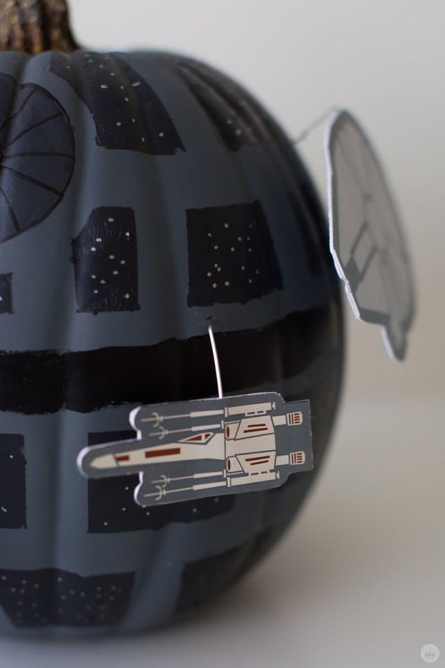 Close-up: Cut-out drawings of Star Wars ships (X-Wing Fighters, Millennium Falcon) circle a black and gray pumpkin painted to look like the Death Star