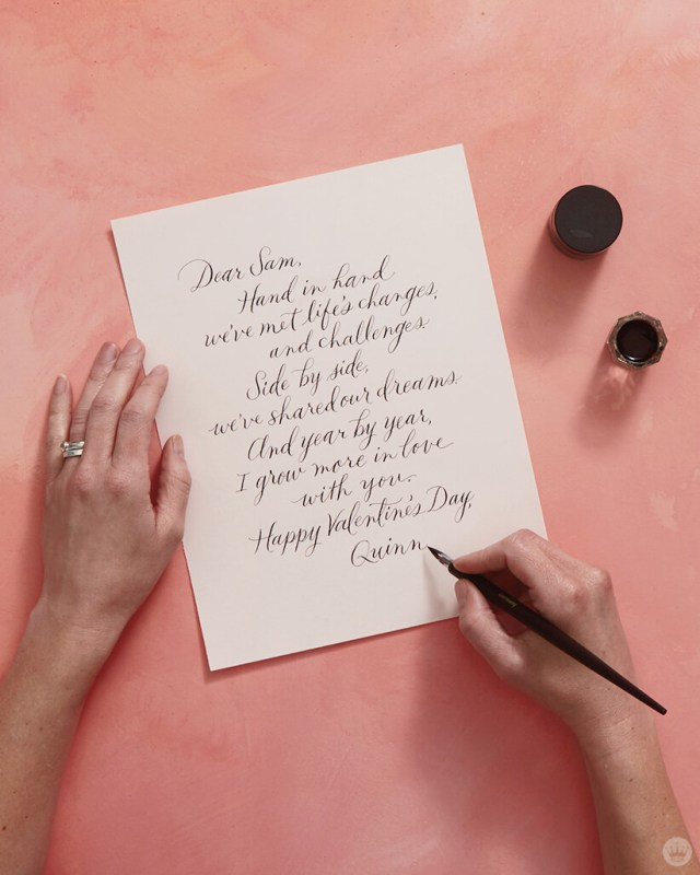 Signing a love note lettered in pointed pen calligraphy