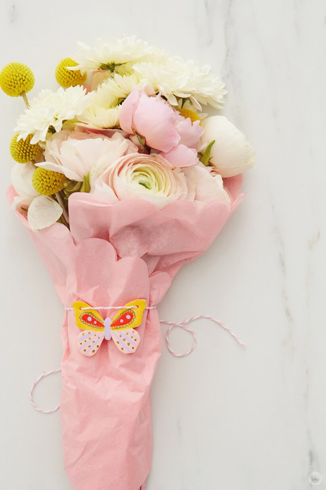 a butterfly clay pin strung around a bouquet of flowers for the DIY Clay gift attachments | thinkmakeshareblog.com