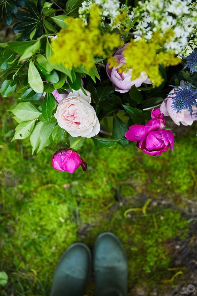 sous-plan de fleurs dans un seau avec deux pieds dans des galoches | thinkmakeshareblog.com