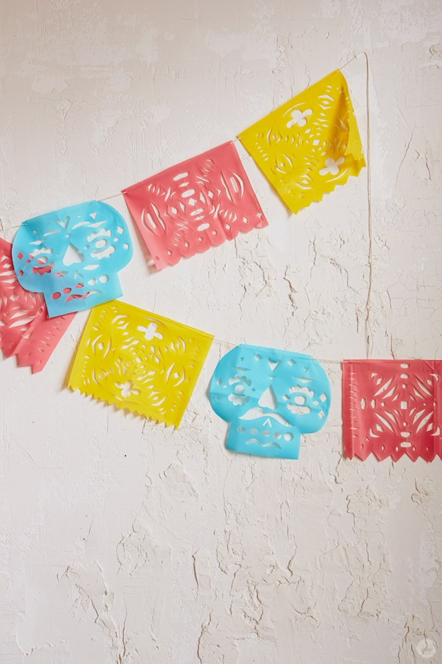 Papel Picado in blue, pink, and yellow with cut-out designs
