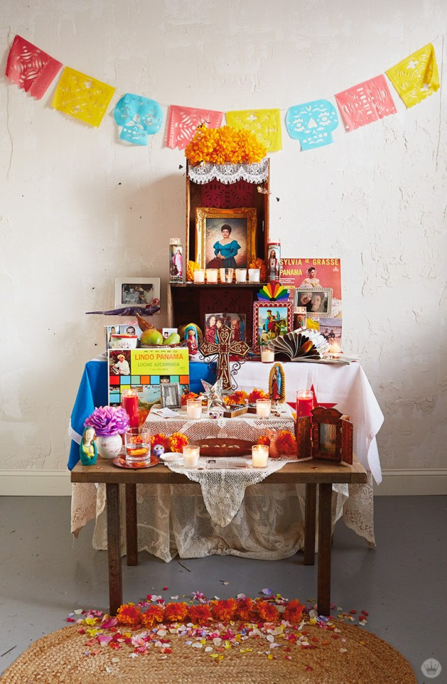 Papel picado banners displayed over an altar created to celebrate Day of the Dead