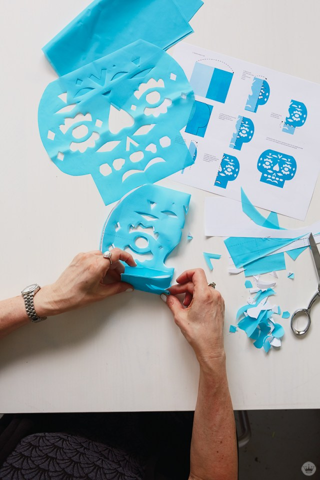 DIY Papel Picado: Folding and cutting along template lines to create skull design