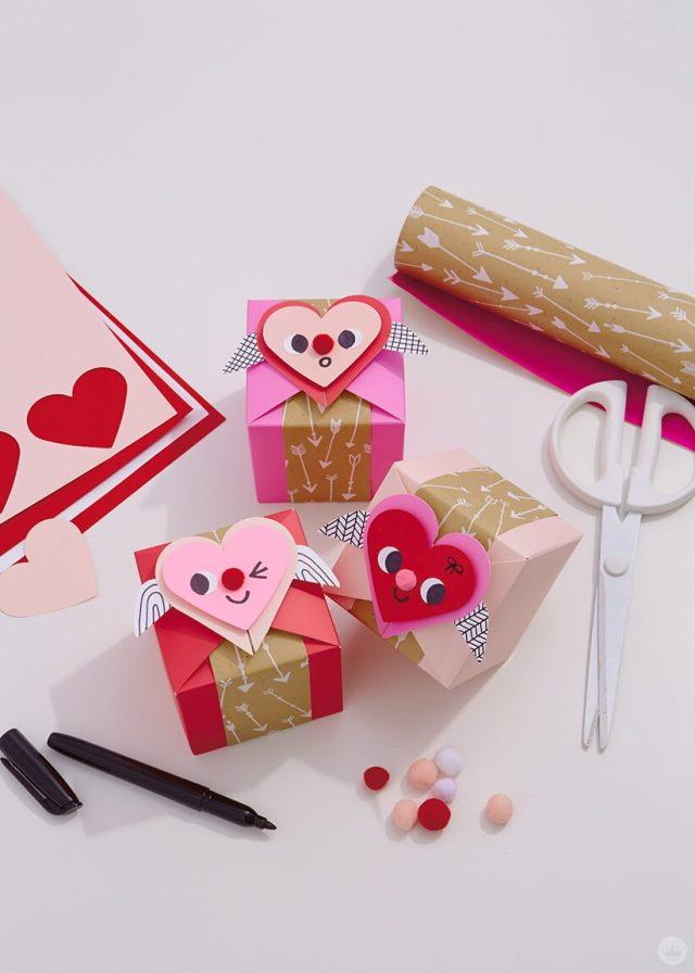 decorated paper wonder gift boxes with the supplies used like scissors, pom poms, and gift wrap | thinkmakeshareblog.com
