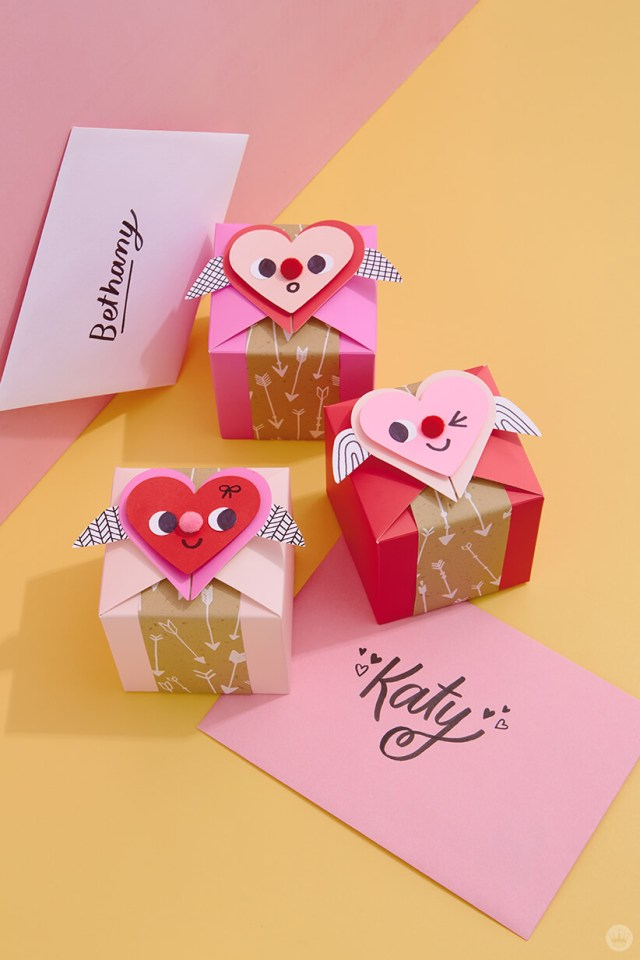 3 cute gift boxes with faces and pom poms on the heart | thinkmakeshareblog.com