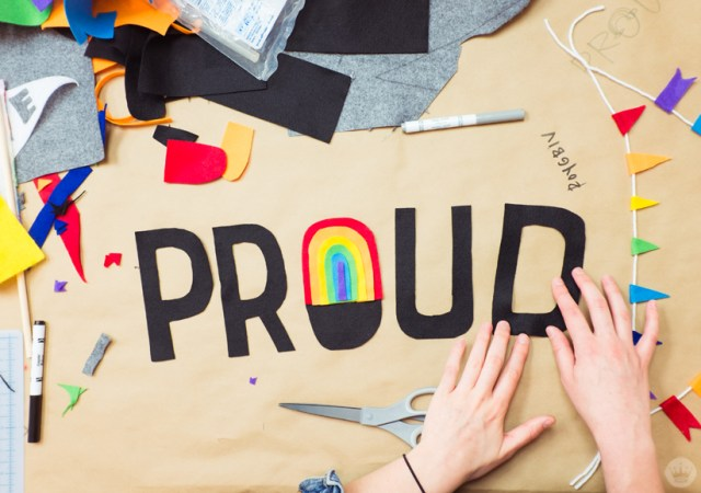 """PROUD"" in felt letters with rainbow in the ""O."""