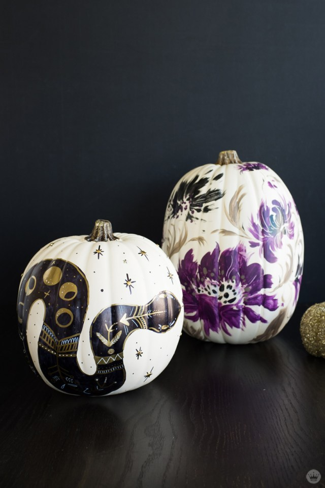 Painted white pumpkins: One with a black and gold snake, the other with purple and black flowers
