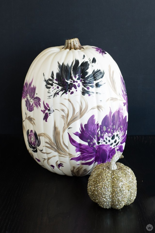Painted white pumpkin decorated with purple and black flowers (also shown: small glitter-covered pumpkin)